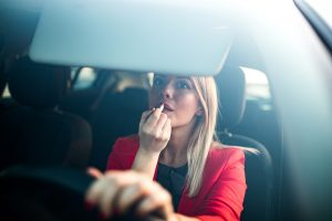 A blonde woman applying lipstick while driving